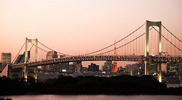Il Rainbow Bridge di Odaiba al tramonto e sullo sfondo la Tokyo Tower.