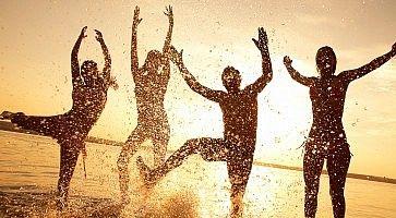 Silhouette di un gruppo di persone mentre si divertono saltando nell'acqua del mare al tramonto.