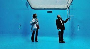 """Due visitatori all'interno dell'opera d'arte """"piscina"""" al Museo d'arte contemporanea di Kanazawa."""