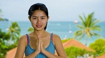 Ragazza thailandese, con la faccia da brava ragazza, con le mani giunte per ringraziare.