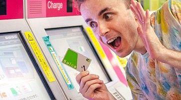 Marco Togni in stazione a Tokyo, con in mano una carta ricaricabile Suica, vicino alle biglietterie automatiche.