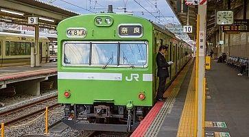 Treno locale JR, di colore verde, diretto a Nara, fermo in stazione a Kyoto.