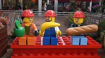 Tre omini lego, vestiti da operai in pausa pranzo.