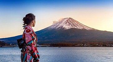 Ragazza asiatica indossa un kimono; sullo sfondo il lago Kawaguchi-ko e il Monte Fuji al tramonto.